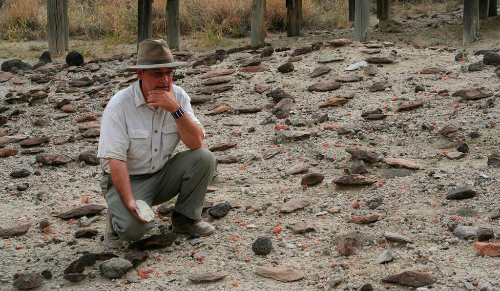 Potts surveys an assortment of Early Stone Age handaxes in the Olorgesailie Basin.