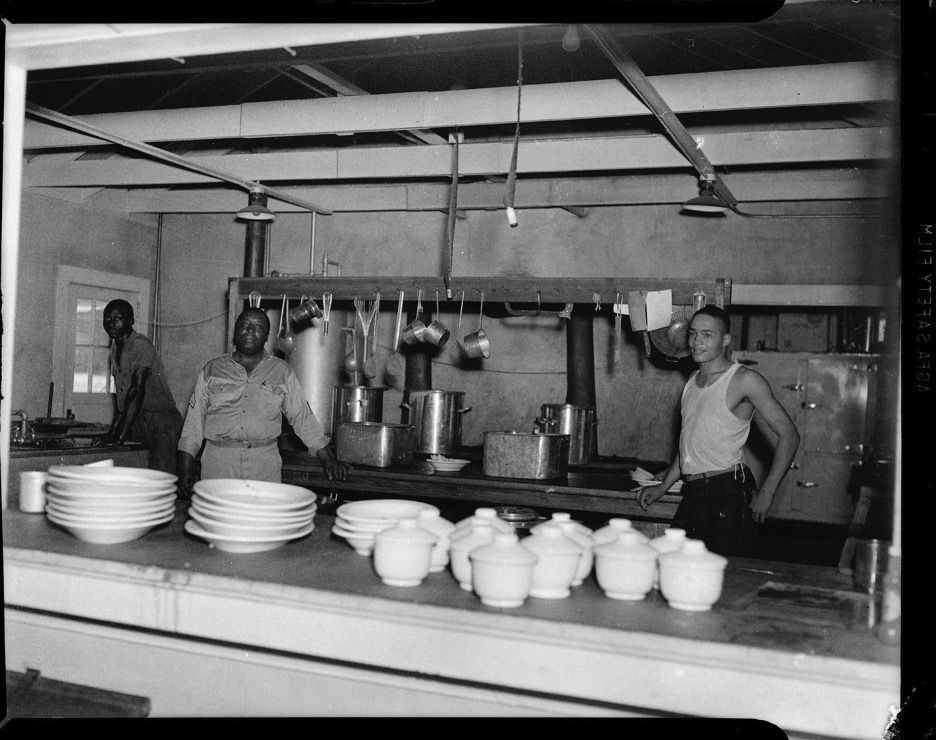 Three men in military mess kitchen