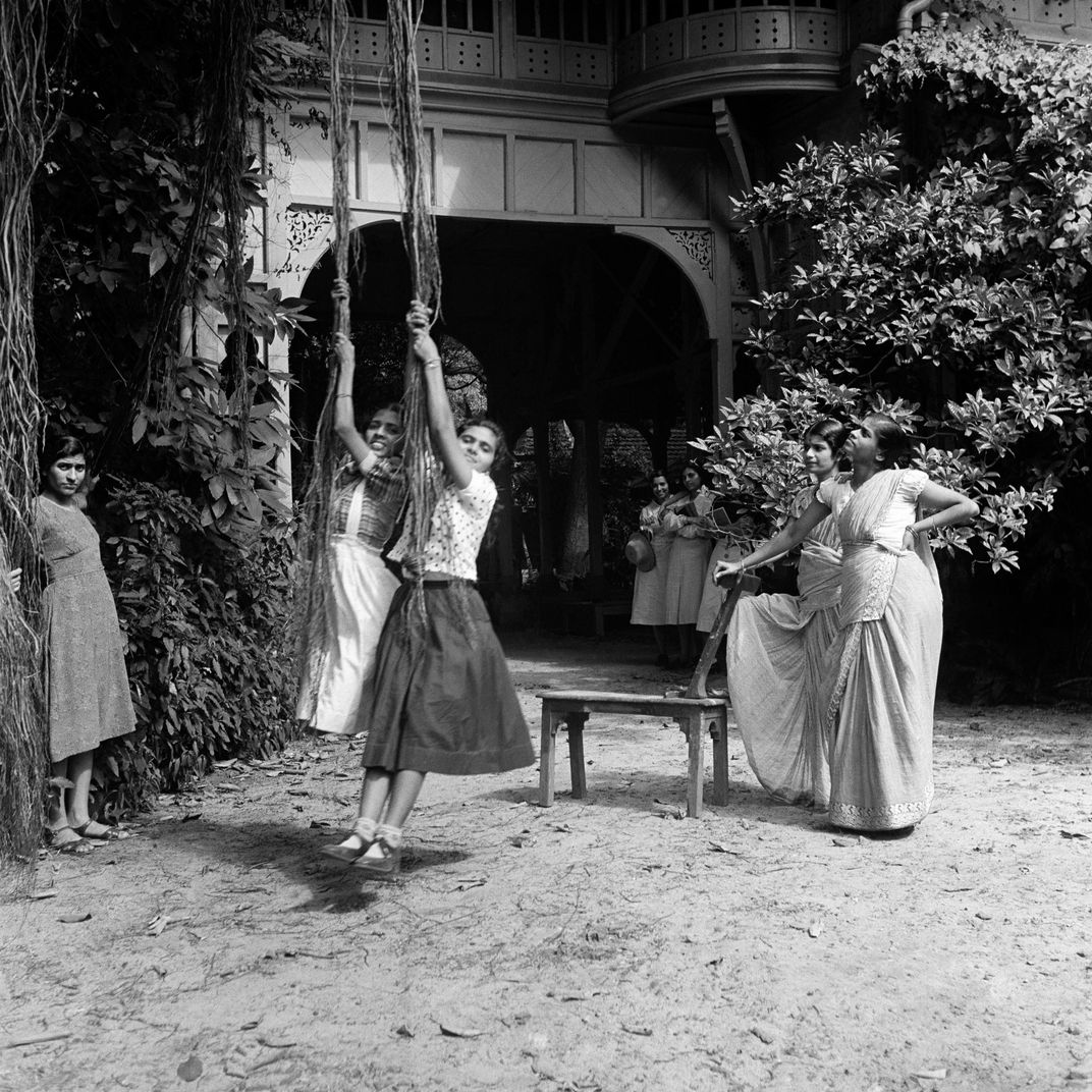 A black and white image of school girls in saris and uniforms playing on rope swings in a courtyard