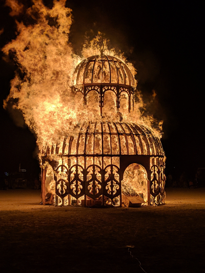 A photograph of a wooden temple burning from a fire.