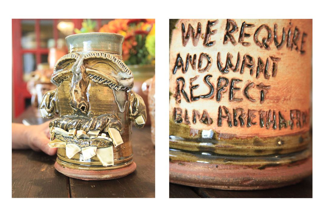Left: Small ceramic jug shaped like a human face, with chipped white pottery for teeth. Right: oom in on the back of the previous jug, with an inscription carved in: WE REQUIRE AND WANT RESPECT - ARETHA FRANKLIN.