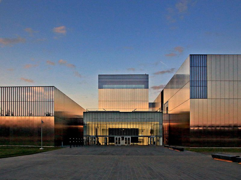 An image of a large, boxy museum with a facade of polished stainless steel and rectangular windows; very modern
