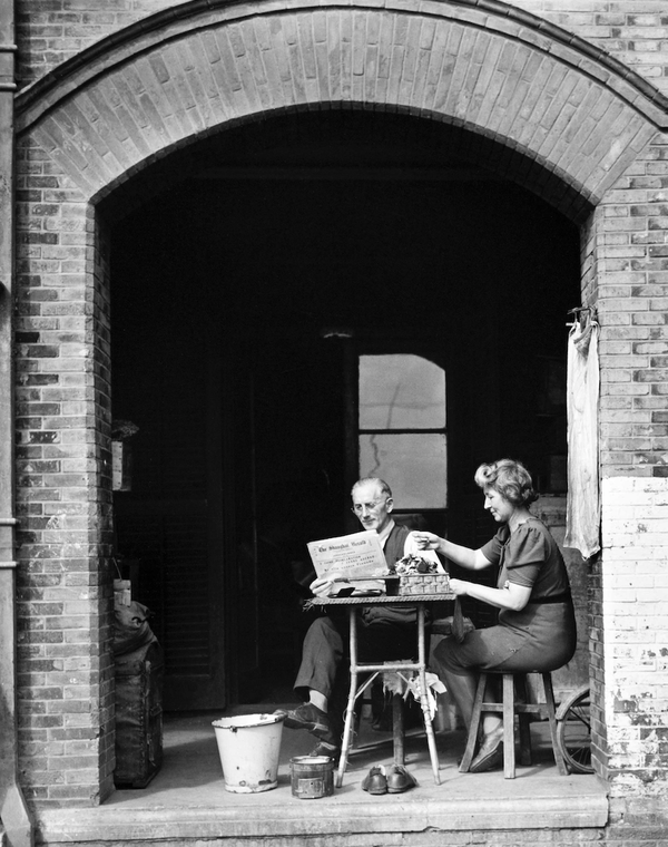 A man and woman sit at a small table in an archway; the man reads the paper and the woman pours a cup of tea
