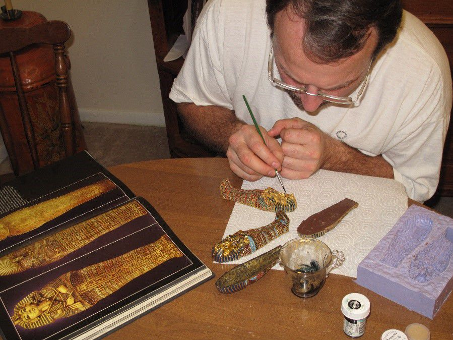 Eric Hollinger sitting at a small, wooden table painting edible gold on a small chocolate sarcophagus.