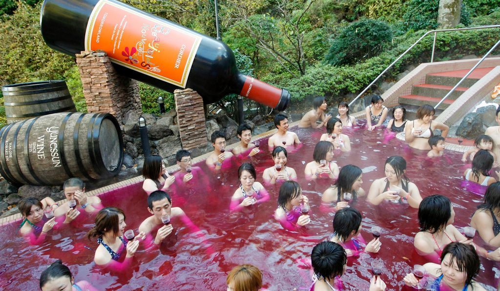 Guests hold their glasses as they bathe in a pool of red at the Hakone Yunessun spa resort, one of Japan's most popular hot spring resorts.