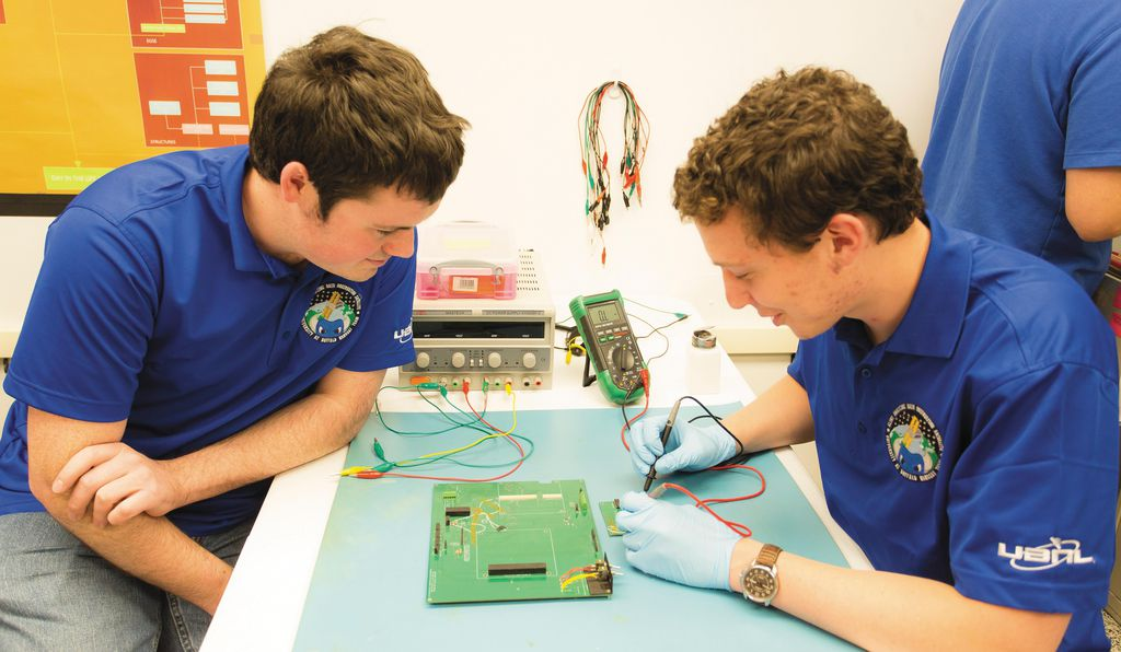 Seamus Lombardo (right) and Andrew Dianetti test student-designed circuit boards before they're installed on nanosats.