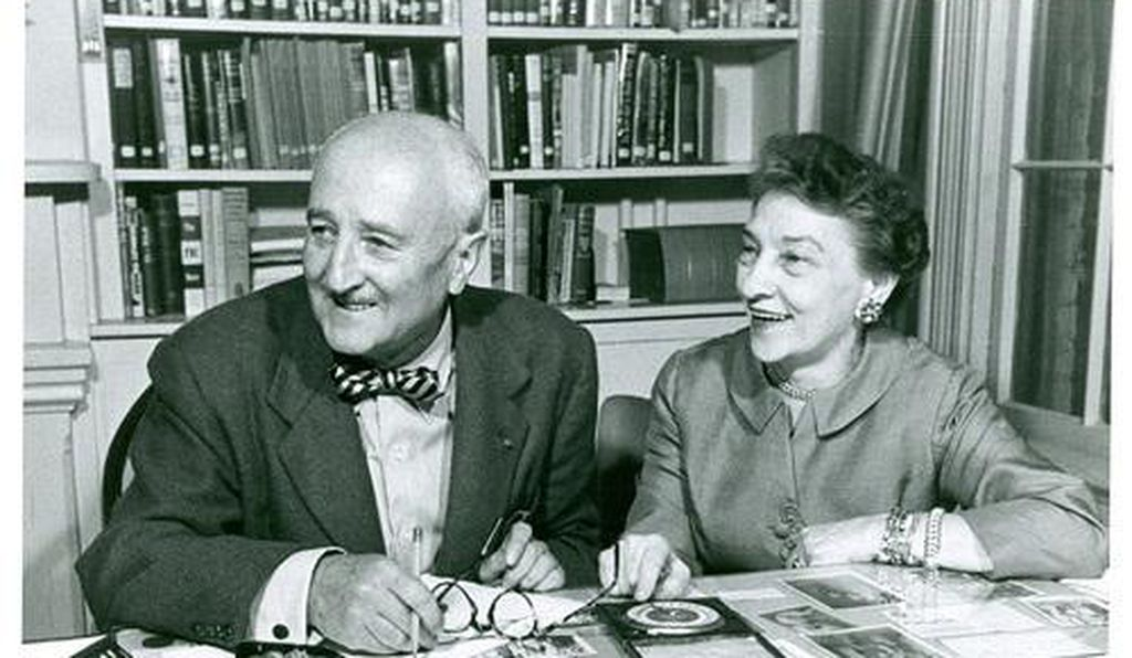 William, left, a white balding man in a bowtie and suit, and Elizebeth, right, a white woman in a suit jacket, sit at a desk with codebreaking materials in front of them; both are elderly