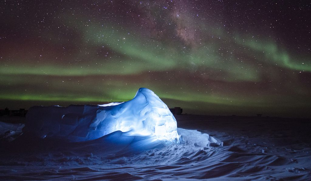 Aurora australis dancing over an LED illuminated igloo in Antarctica.