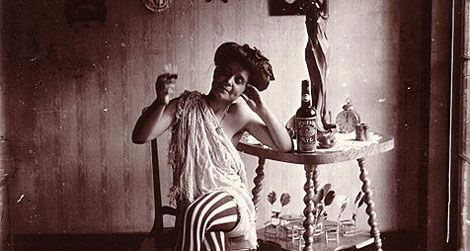 Storyville. Seated woman wearing striped stockings, drinking
