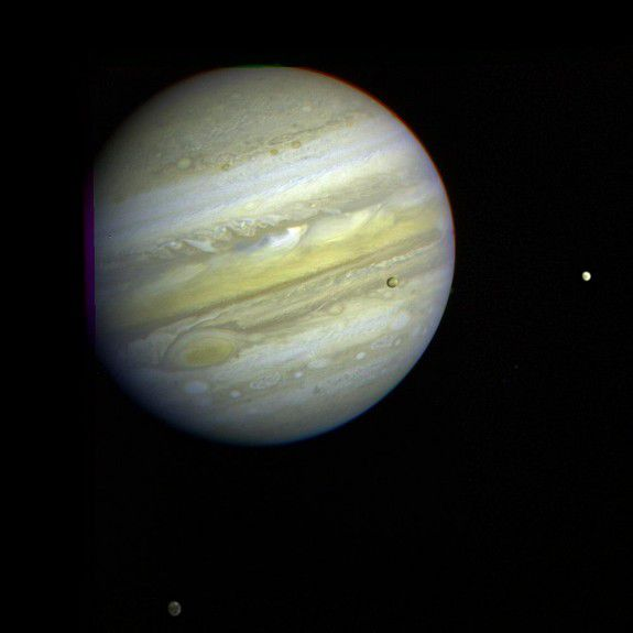 Three of Jupiter's moons, Callisto, Io, and Europa can be seen orbiting the gas giant.