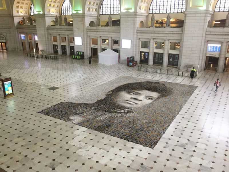 An aerial view of the mosaic, with two people walking nearby for scale; the mosaic takes up 1,000 square feet of floor in Union Station. The station is currently mostly empty due to the Covid-19 pandemic.