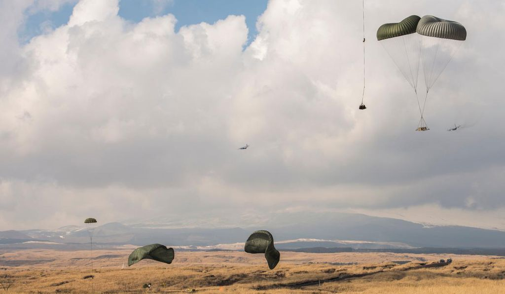 Two C-130 Hercules aircraft complete pallet drops at the base of Mt. Fuji, Japan, Feb. 2, 2016. The 374th Logistics Readiness Squadron spent hours constructing each pallet and packing the parachutes.