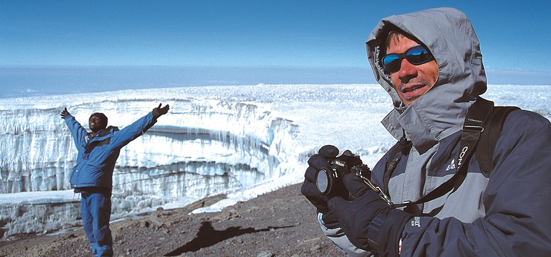 Hikers take a photo with one of Mt. Kilimanjaro's large glaciers