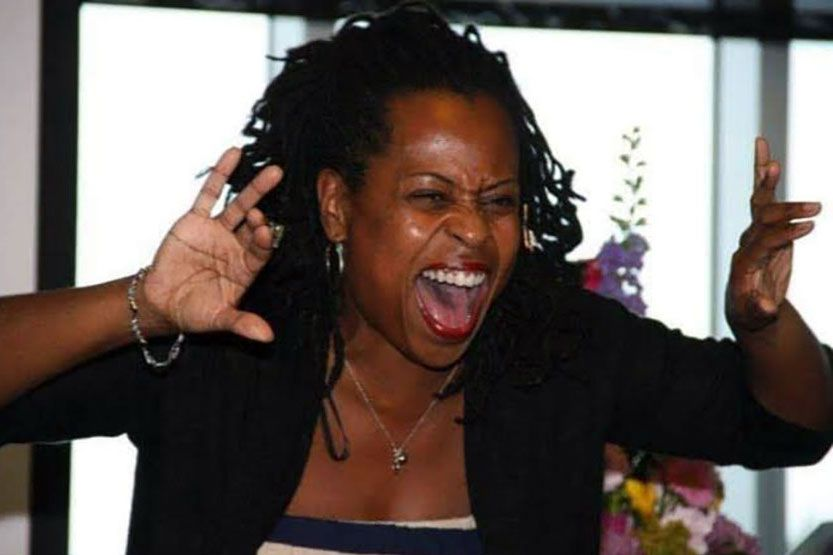 A Black woman acts out a part in a story, her hands raised as if pulling back curtains, her face menacing, like an animal about to attack.