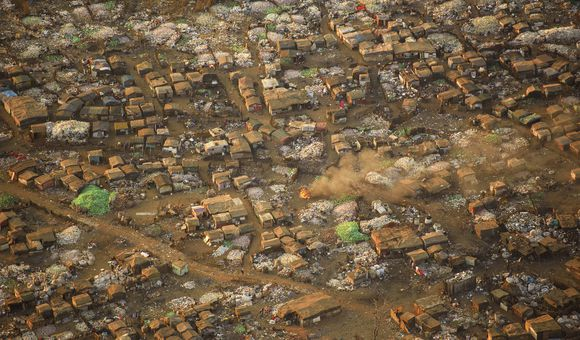 Thousands of people live in similar conditions in and all around Johannesburg, South Africa. To survive, many of them collect bottles and other recycling materials. Aerial image (shot from a plane at sunset).