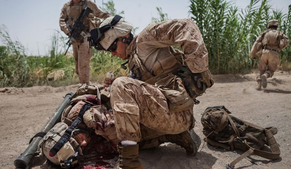 Team leader Hopp leans over Jimenez to stop the bleed. The IED was set off using a command wire that stretched into a nearby field and was activated with a motorcycle battery.