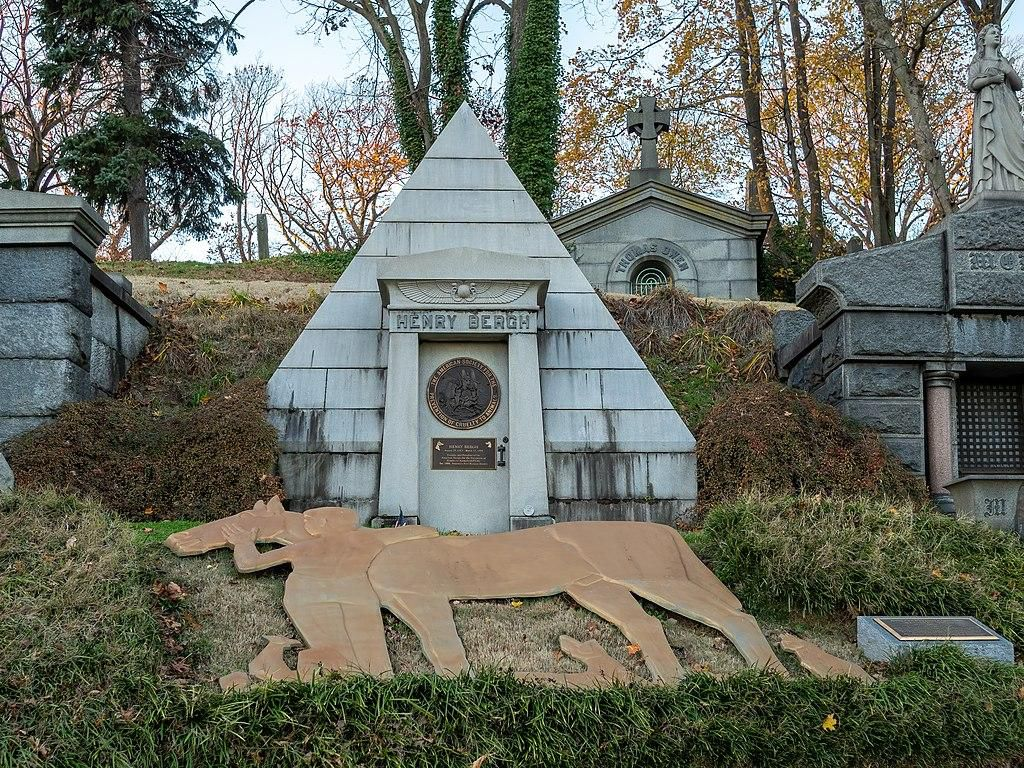 Pyramid-shaped mausoleum with a statue of a man humming a horse outside