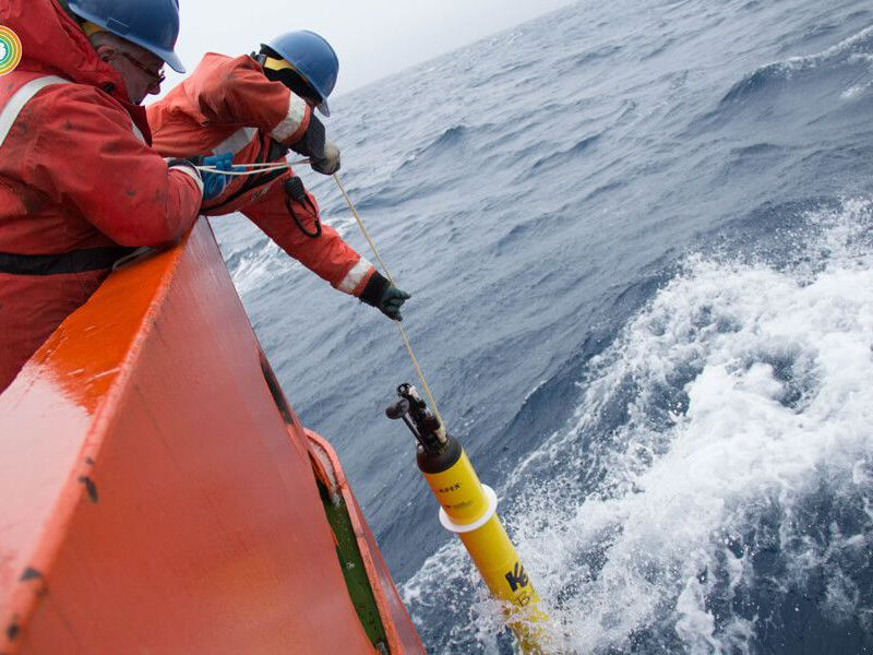 Researchers lean over side of boat with device to measure CO2