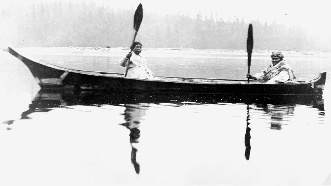 Two people in a canoe out on the water. Black-and-white archival photo.