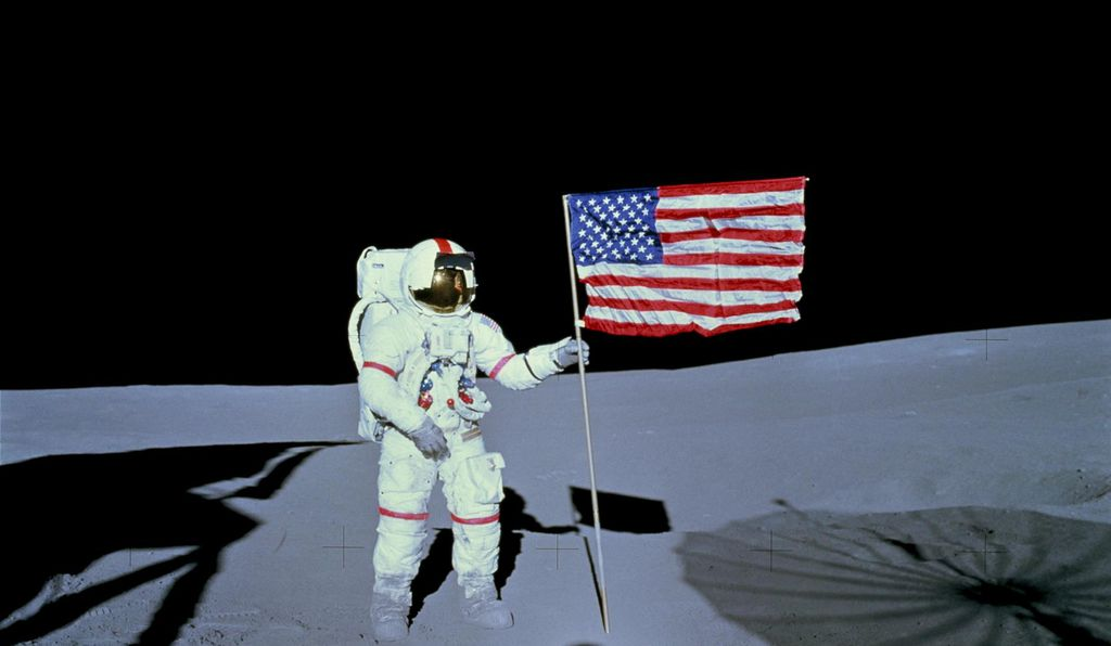 Astronaut Alan B. Shepard Jr., commander of the Apollo 14 lunar landing mission, stands by the deployed United States flag on the lunar surface.