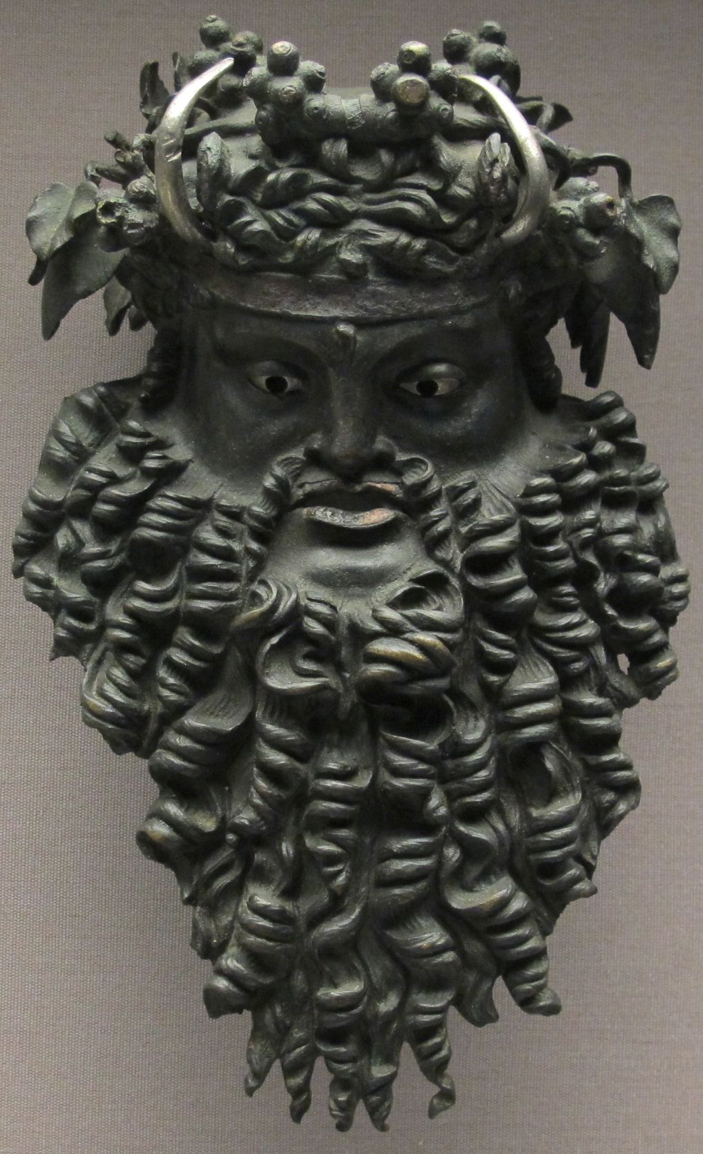 A previously discovered bronze mask of Dionysus