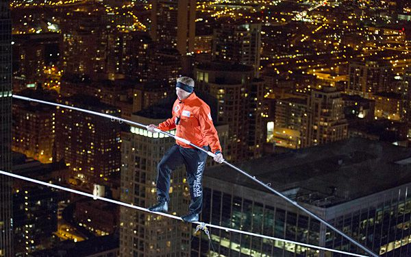 Daredevil walks on wire between two skyscrapers