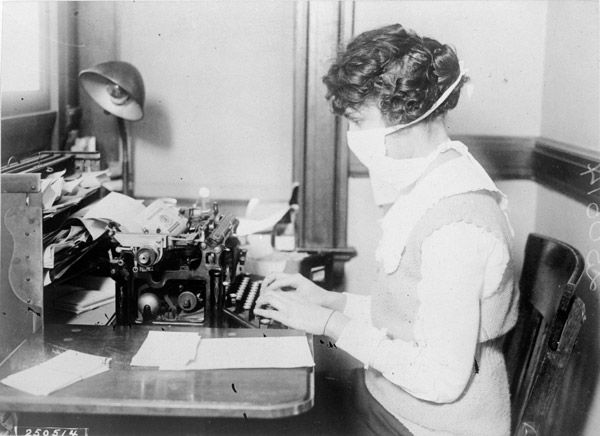 woman wearing a mask and typing