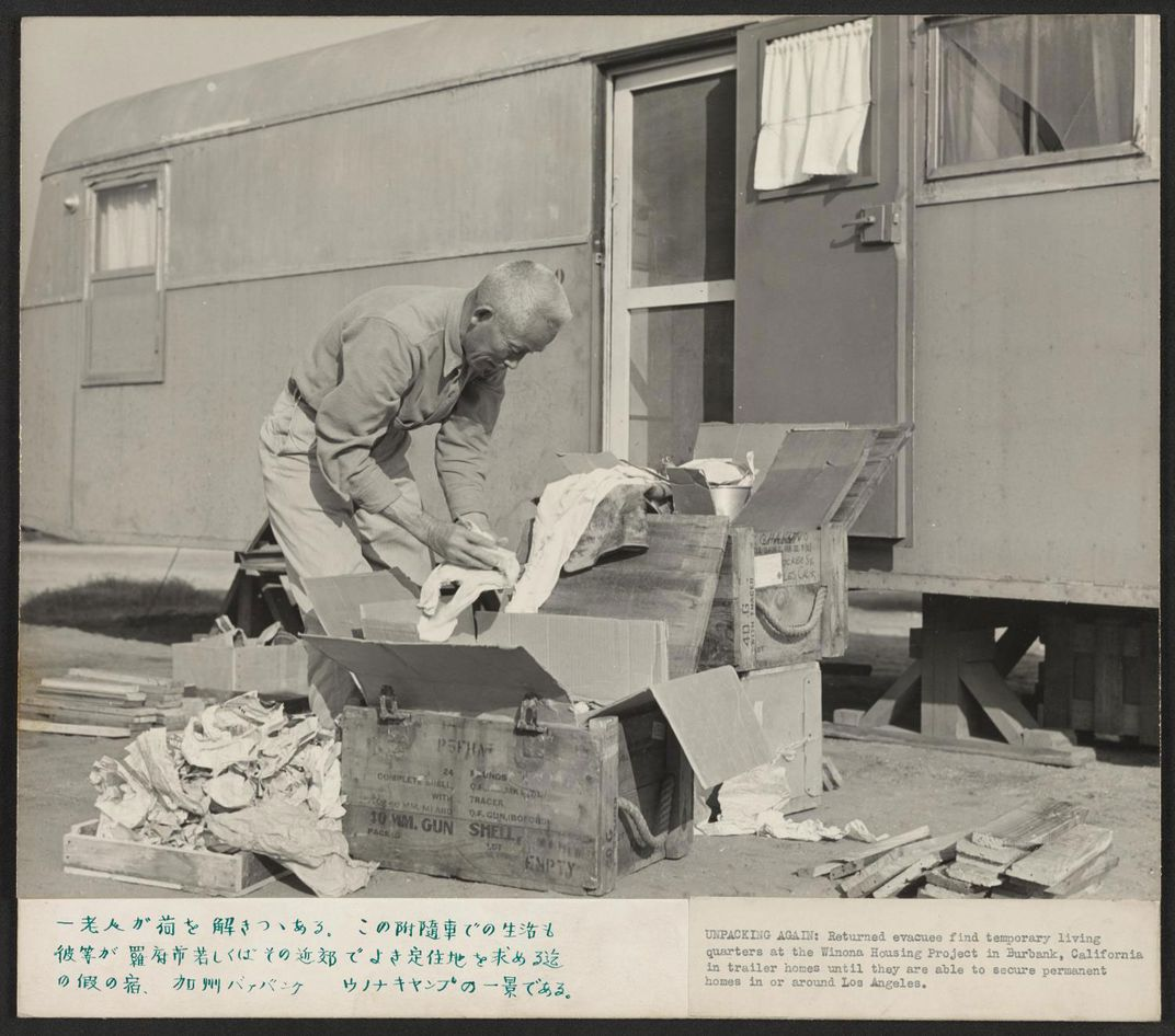 A black and white photo shows a man standing bent over in front of a trailer unpacking cardboard boxes.