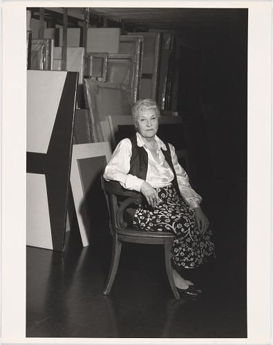 A black and white photograph of a woman sitting in a chair in front of canvases.