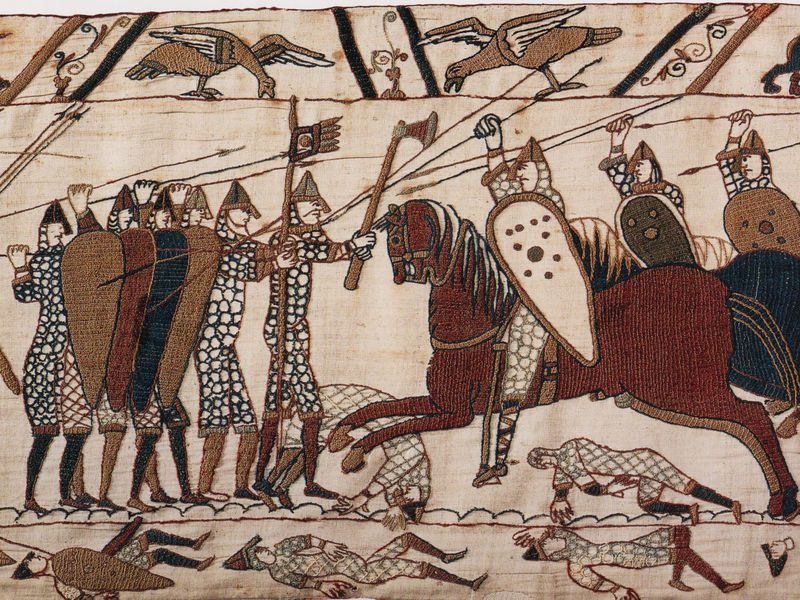 Part of scene 52 of the Bayeux Tapestry. This depicts mounted Normans attacking the Anglo-Saxon infantry.