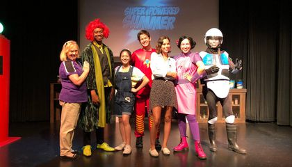 Young Ambassador, Mia Cooper and her supervisor Cathy posing with the cast of the superhero show