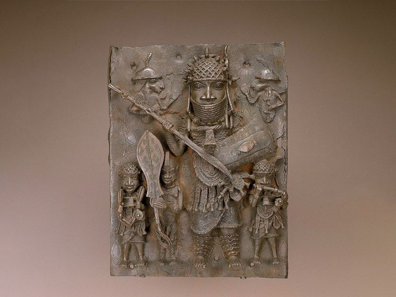 A brown metal plaque that is intricately carved with figures, including a large central figure wearing armor and towering over at least three smaller people standing beneath