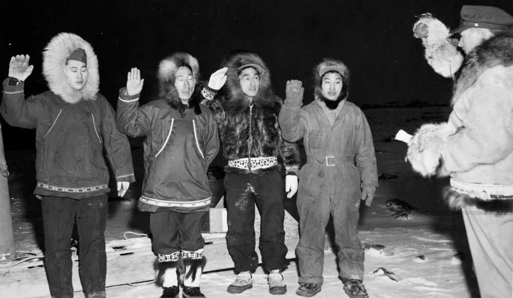 A military officer swears in four Alaska Territorial Guardsmen for assignment in Barrow, Alaska, on the shore of the Arctic Ocean.