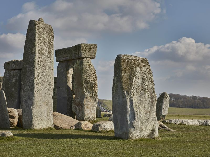 A view of the iconic rocks of Stonehenge on green grass, with a sloping hill visible between two stones in the distance and a line of traffic