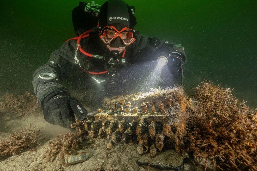 A person wearing scuba equipment and red goggles floats in murky green water and shines a flashlight above an item on the ocean floor, overgrown with algae but resembling a typewriter