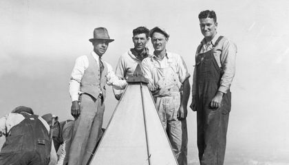 Man posing with construction workers at the top of the Washington Monument