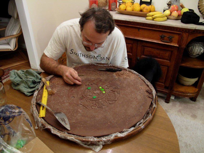 Eric Hollinger sitting at a small, wooden table bent over a large round slab of solid milk chocolate.