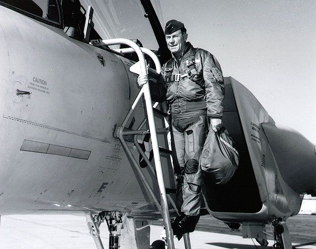 Chuck Yeager standing on ladder on outside of aircraft.