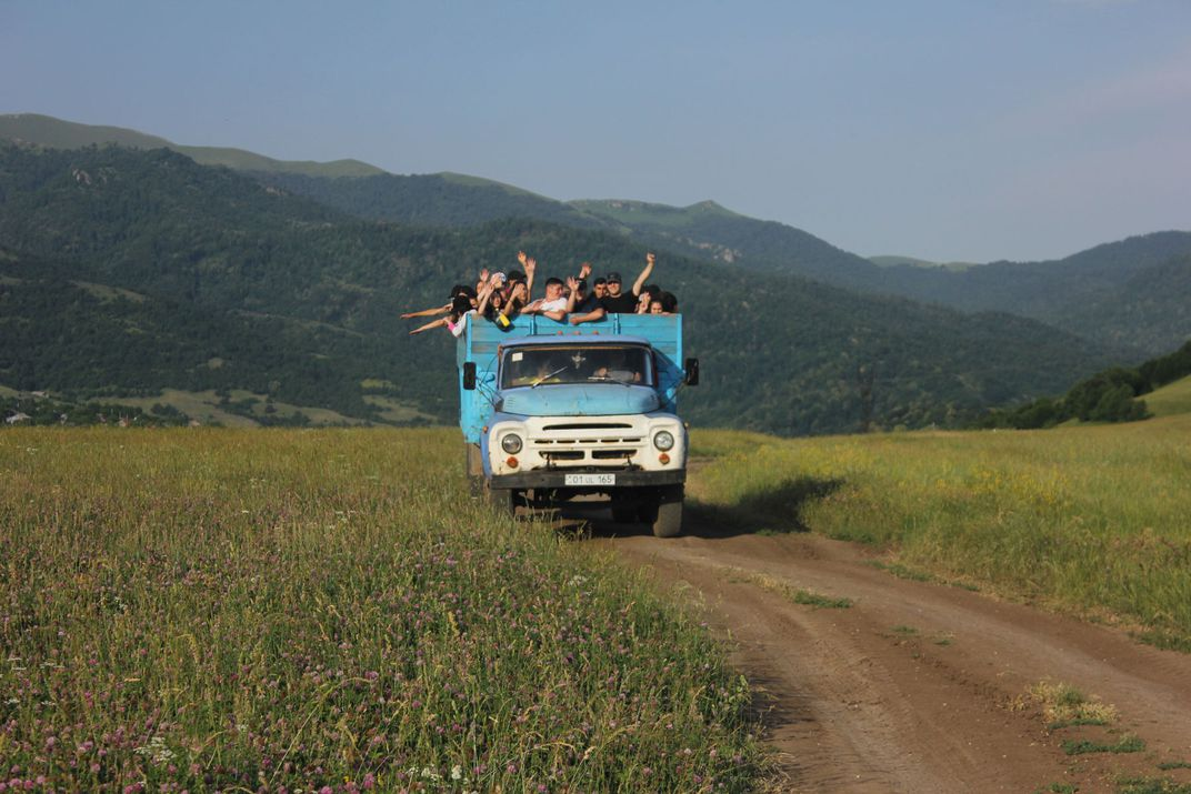 A blue truck filled with people drives through a green field.