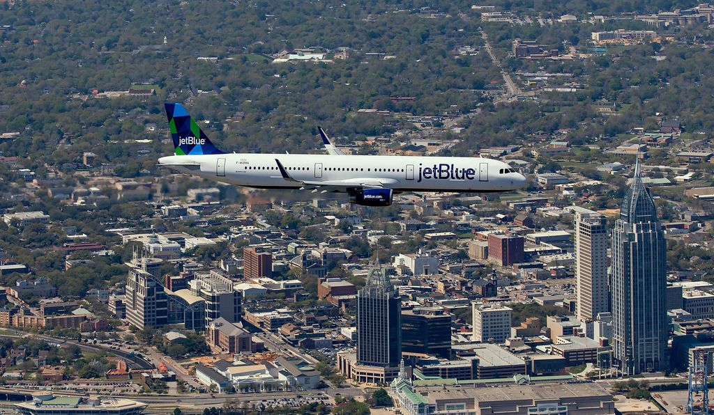 The first Airbus built on U.S. soil went to JetBlue. The A321 soars over a Mobile skyline dominated by the RSA Battle House Tower.