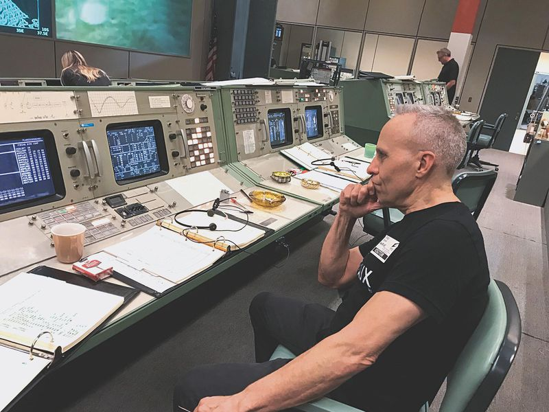 Doug Drexler seated in chair on mission control set