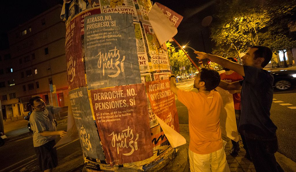 Barcelona, Catalonia, Spain. September 17. Activists from the pro-independence coalition Junts pel SÌ (Together for Yes) stick posters at worker district of 9 Barris in the city of Barcelona.