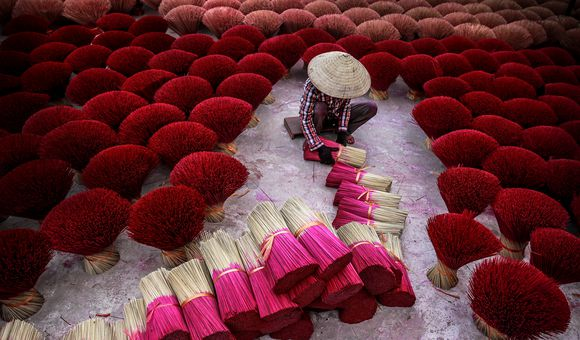 Decoratively dyed bundles of incense dry in Quang Phu Cau, a commune in Hanoi, Vietnam. In Buddhist countries like India,  China, Thailand, Japan, Vietnam.. incense is an irreplaceable part of traditional festivals and religious ceremonies. It is also considered as a sacred bridge to connect the visible life of human beings and the world of heaven, earth and gods. Incense has been a hallmark of Orient culture for thousands of years.