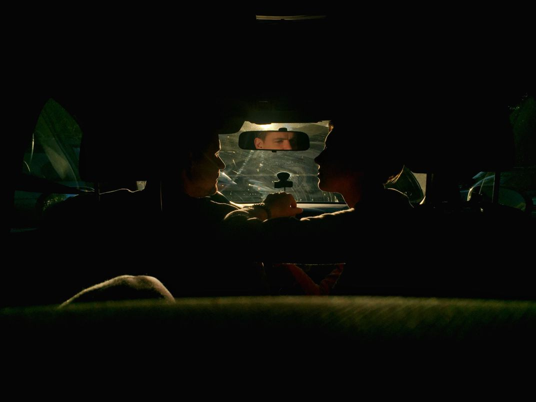 A family sits in a dramatically lit car