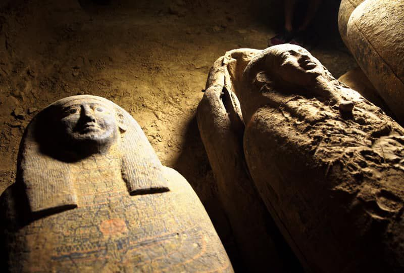 Two coffins carved on the outside to resemble human faces and bodies, lying next to one another in a dusty chamber