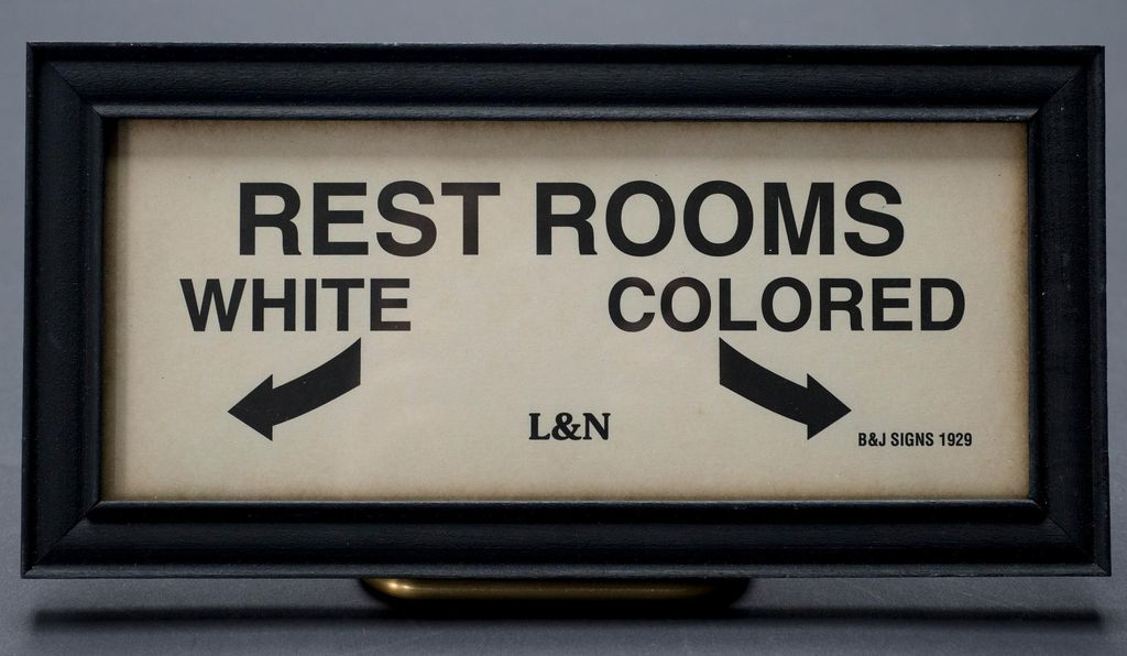 A reproduction of a historic sign directing people to racially segregated restrooms.