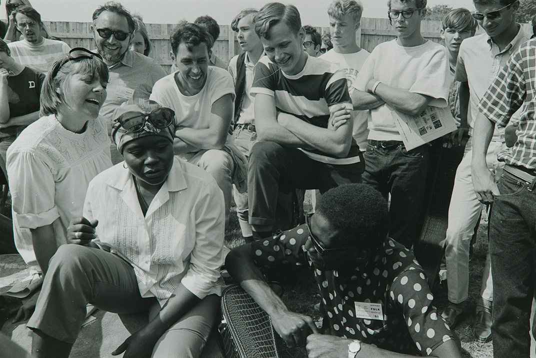 Black-and-white photo of a group of young people gathered outside, singing and smiling.