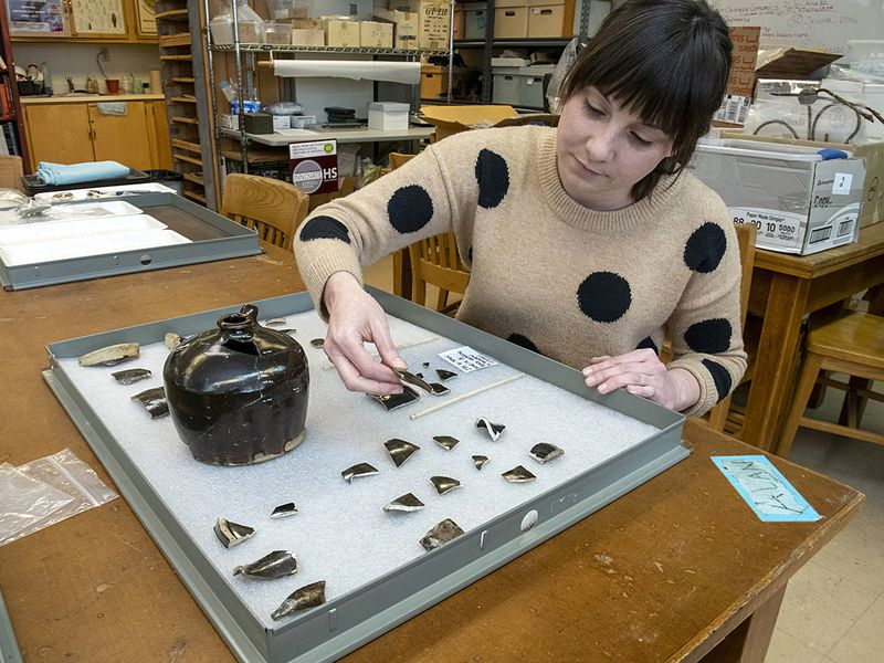 Archaeologist examines fragments of Chinese pottery