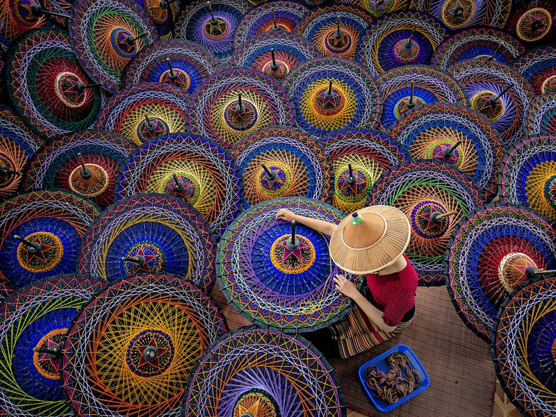 A girl is working in the traditional umbrellas . The Patterns and Colours are so interesting . It is also the art of her life.