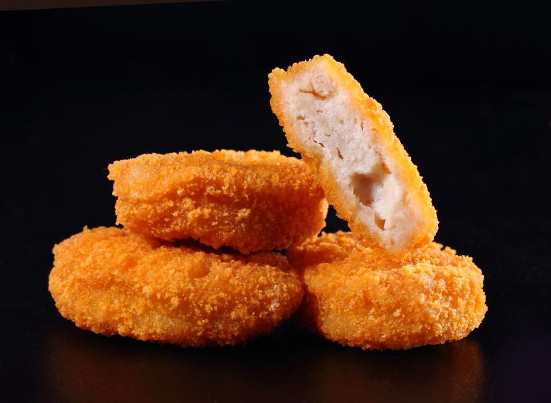 A close-up shot of three chicken nuggets stacked up in front of a black background. On top is one chicken nugget, cut in half, with the insides facing the camera.